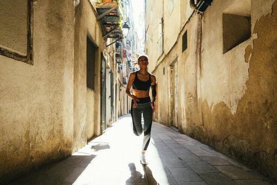 Young latin woman running on the street. Urban life.