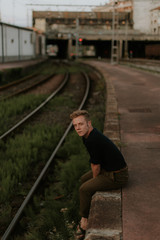 young man sitting in te border of the railway