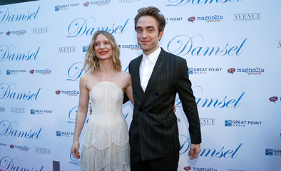 """Cast members Pattinson and Wasikowska pose at the premiere for the movie """"Damsel"""" in Los Angeles"""