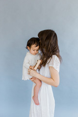 Portrait of mom holding baby against backdrop