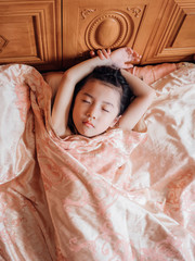 Asian little girl lying on bed