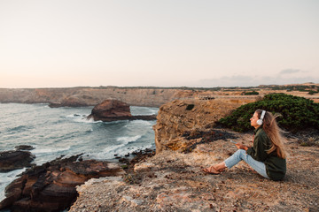 A single woman relaxing with music at coast of Atlantic Ocean, at Portugal.