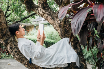 Asian man reading book in zen style traditional Chinese clothing