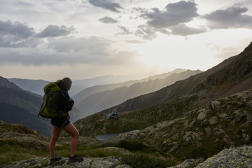 Young woman backpacker enjoying the sunrise in the mountains
