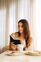 Woman having breakfast with notebook