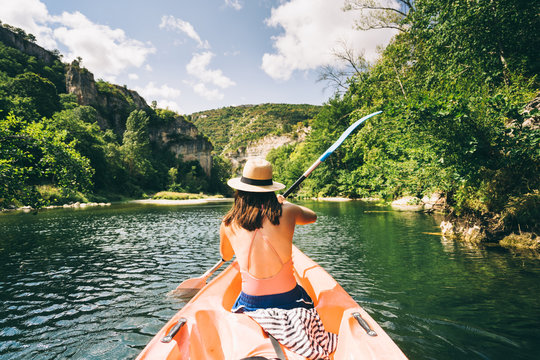 paddler in a canoe on a river in a lush green valley