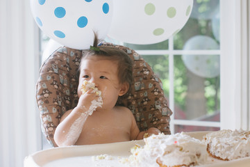 Baby eating first birthday cake
