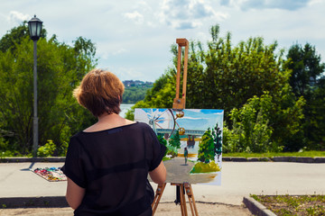 A young blonde female artist in a black T-shirt and jeans paints on canvas and an easel with oil paints in a city park on a sunny day. Drawing on an open air