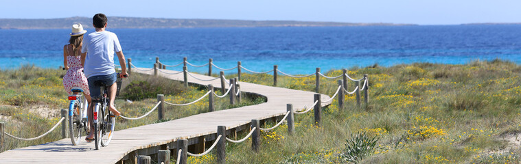 Couple riding bikes on Formentera Island, template