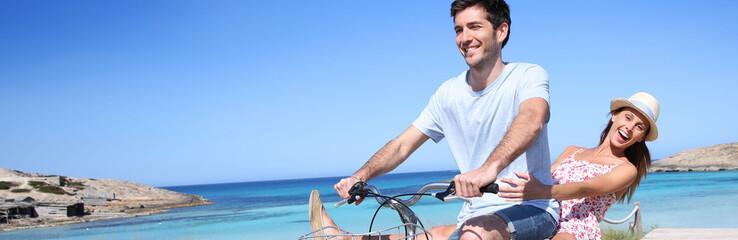 Man giving bike ride to girlfriend on beautiful Island, template