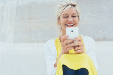 Middle-aged laughing woman using mobile phone