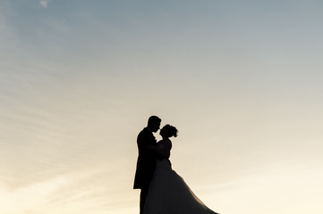 Silhouette of bride and groom embracing each other at sunset