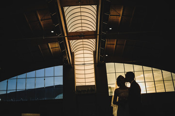 Silhouette of bride and groom kissing in an abandoned industrial ship at sunset