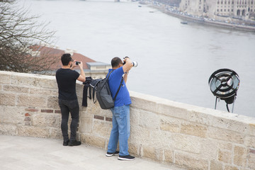 Two men take pictures with one professional camera, another with a phone