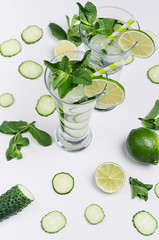 Cold natural refreshing cocktail with slices cucumber, lime, mint, ice, straw on white wood plank, top view, closeup.