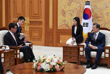South Korean President Moon Jae-in talks with Japanese Foreign Minister Taro Kono during their meeting at the presidential Blue House in Seoul