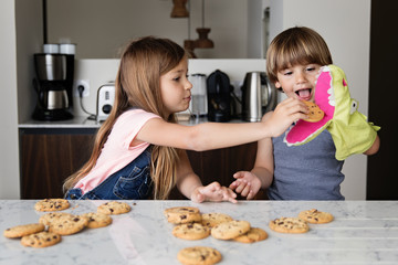 Kids pretending to feed a puppet with cookies at kitchen table