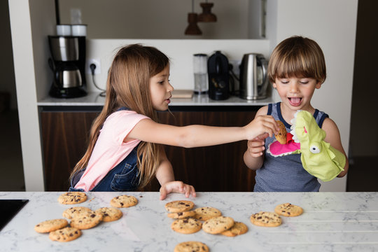 Siblings pretending to feed a puppet with cookies at kitchen counter