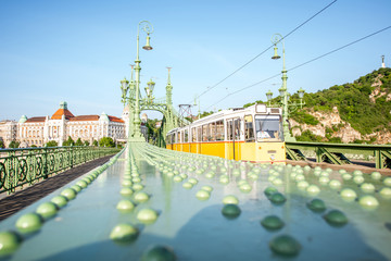 View on the famous Liberty bridge with old yellow tram during the morning light in Budapest, Hungary