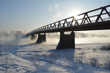 Bridge over the river, which does not freeze. Winter scene in Siberia, Russia.