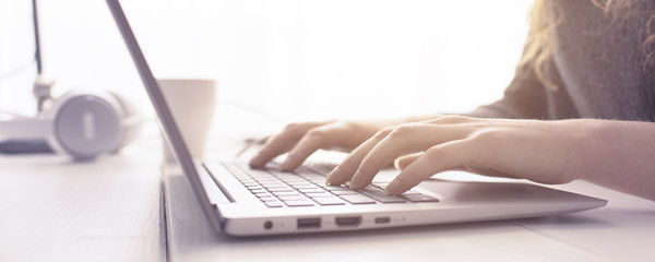 Woman sitting at desk and connecting with her laptop, she is working and typing on the keyboard, hands close up