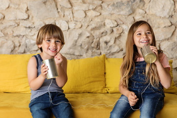 Smiling kids playing with tin can telephone on yellow couch