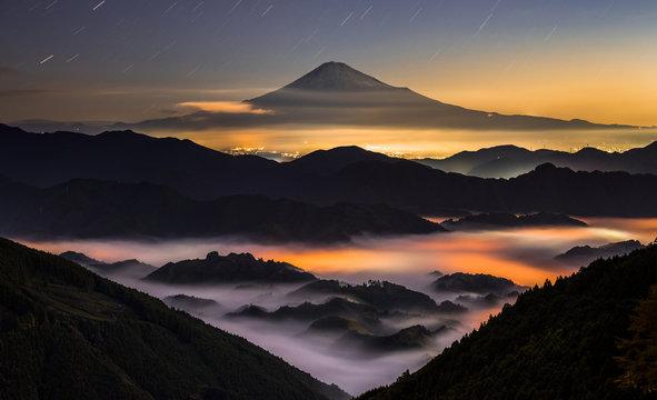 夜の雲海に浮かぶ富士山と星空