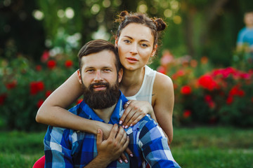 Close up portrait of attractive brunette woman and her handsome bearded boyfriend in park. Bush of roses flowers in the background