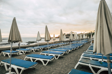 umbrellas and seats in closed business at the beach after a day full of sun and vacation outdoor leisure concept. colors and relaxed time in sunset sky