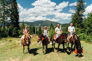 group of people riding horses in the mountains
