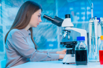 Young pretty girl student peering through microscope in science classroom