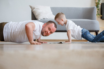 Photobook of father and son pushing on floor near sofa