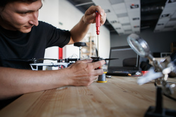 Photo of man with screwdriver fixing square copter at table