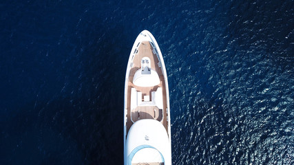 Aerial drone bird's eye top view photo of luxury yacht with wooden deck docked in deep blue waters of Mykonos island, Cyclades, Greece