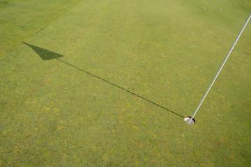 Lochfahne wirft langen Schatten auf das Grün vom Golfplatz