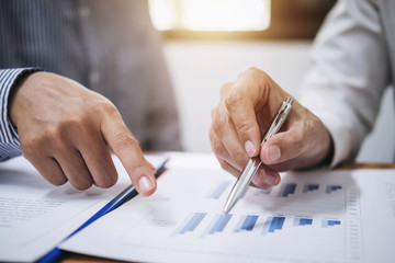 Two business team working and discussing Financial investment on report with calculate Analyze business and market growth on financial document data graph