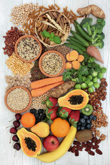 Healthy high fibre food with grains, legumes, whole wheat pasta, fresh fruit, vegetables, nuts, seeds and cereals. Top view on rustic background.