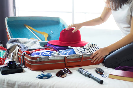 Travel and vacation concept, happiness young woman packing a lot of her clothes and stuff into suitcase on bed prepare for travel and journey trip in holiday