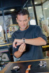 Man trying on watch on jewellers