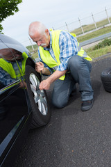 retired man has to change punctured wheel