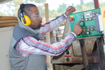 man with ear protection working in a factory