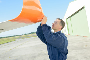 Mechanic inspecting wing of glider