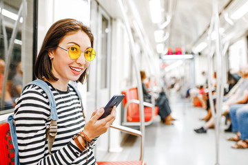 Asian Woman hipster tourist travels in a subway and using the smartphone in a modern train carriage