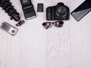 Flat lay top view of traveler accessories on white wooden background. DSLR and action camera, tripod, flash, smartphone