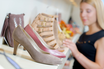 Shoes on shelf, unfocused lady in background