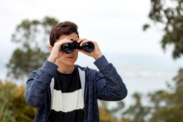 Teenager guy looking with binoculars