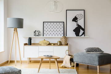 Wooden table and grey pouf in bright flat interior with posters and lamp next to cabinet. Real photo