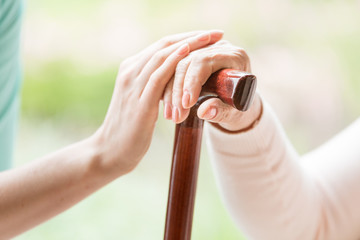 Close-up of caregiver holding hand on hand of senior person with walking stick