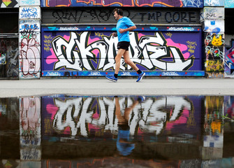 A jogger is reflected in a puddle as he runs past Graffiti on the bank of Donaukanal channel in Vienna