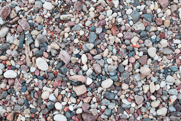 Different color, size and shape stone pebbles on seaside as natural abstract textured background.